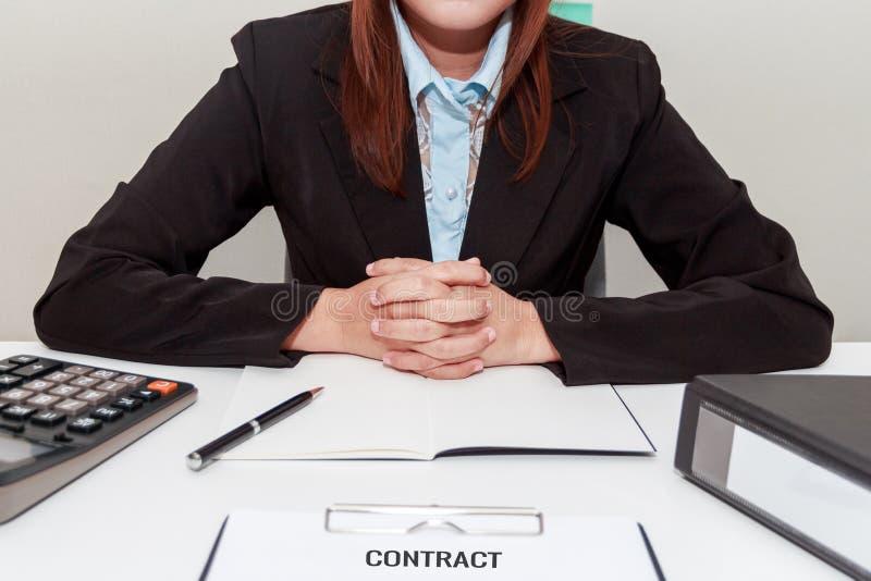 握她自己的手的女实业家,当坐在书桌-标志时 库存照片