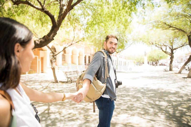 握妇女` s手和带领她的英俊的旅客人  免版税图库摄影