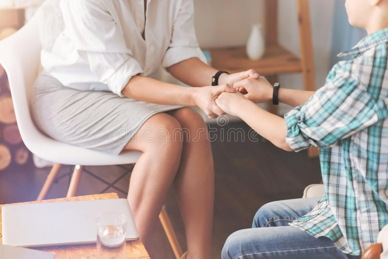 握宜人的男生的手的专业心理学家 图库摄影