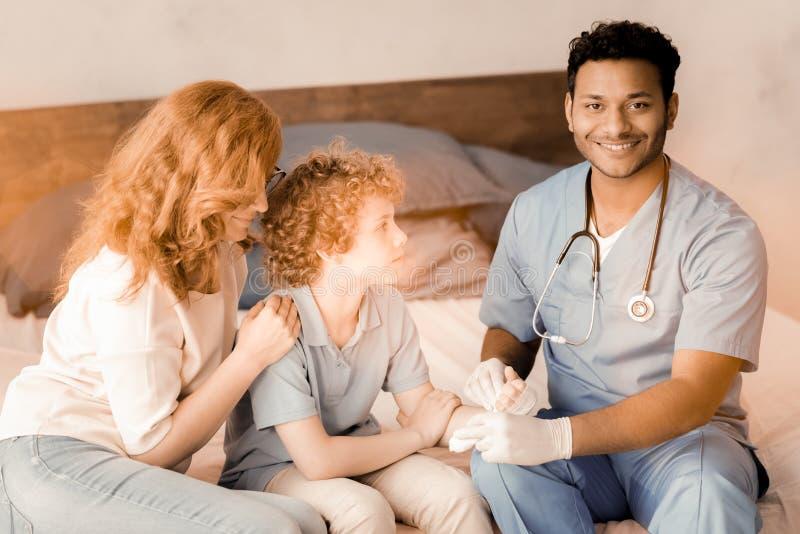 握患者的手的微笑的国际医生 免版税图库摄影