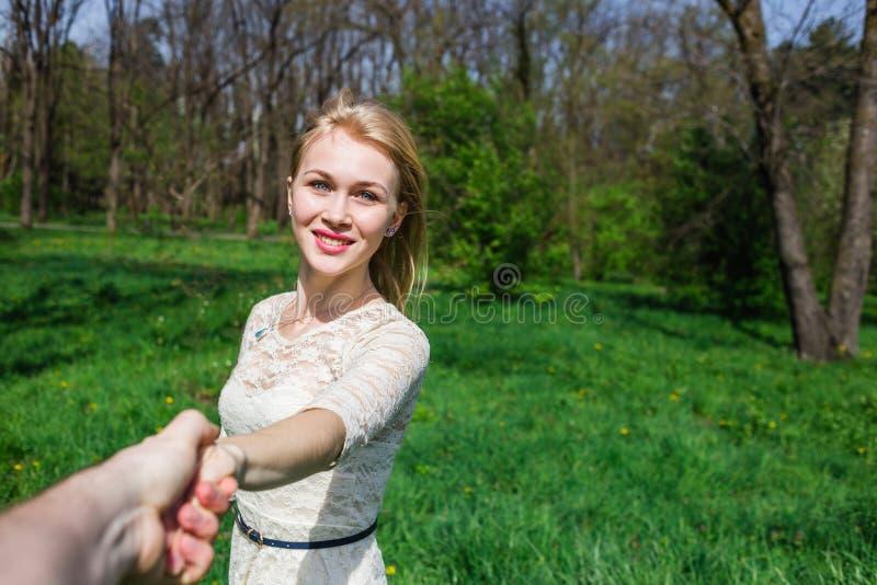 握我的手和跳舞在开花庭院里的可爱的愉快的金发碧眼的女人 观点 免版税库存图片
