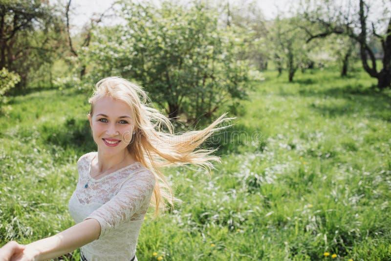 握我的手和跳舞aroundin开花庭院的可爱的愉快的金发碧眼的女人 观点 免版税库存照片