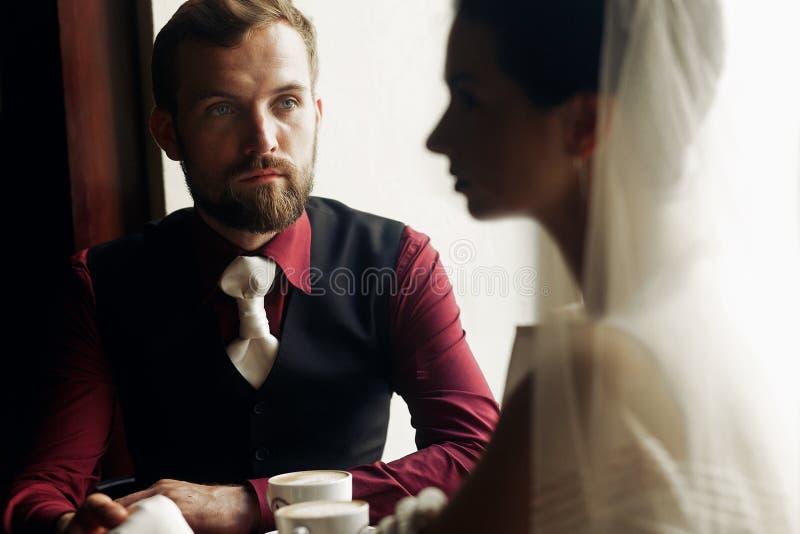 握手和喝在咖啡馆的豪华婚礼夫妇咖啡 免版税库存照片