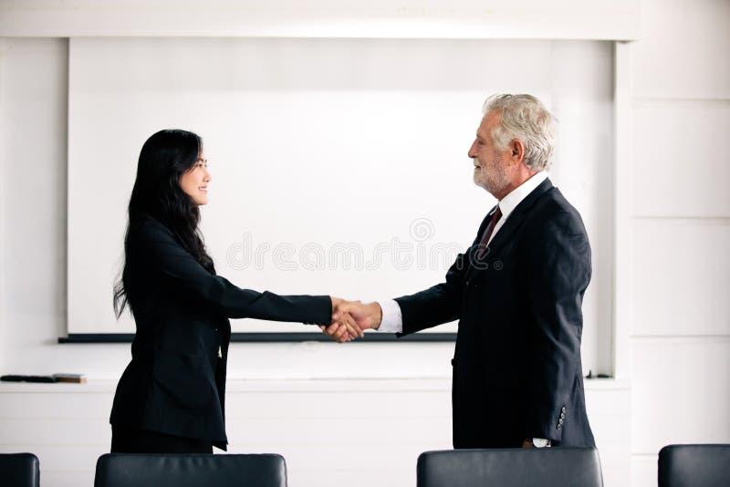 握手和微笑他们的协议签合同和结束会议的商人 免版税库存图片