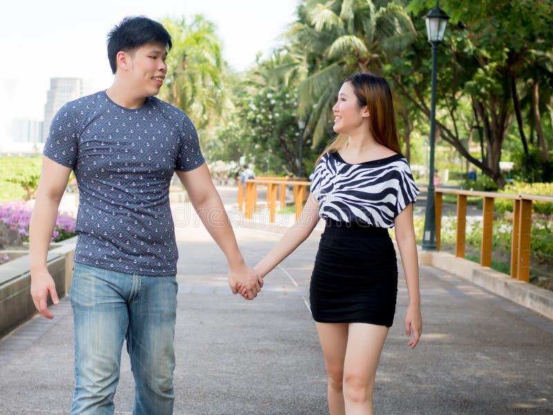 握手和散步在绿色自然的亚洲夫妇 库存照片