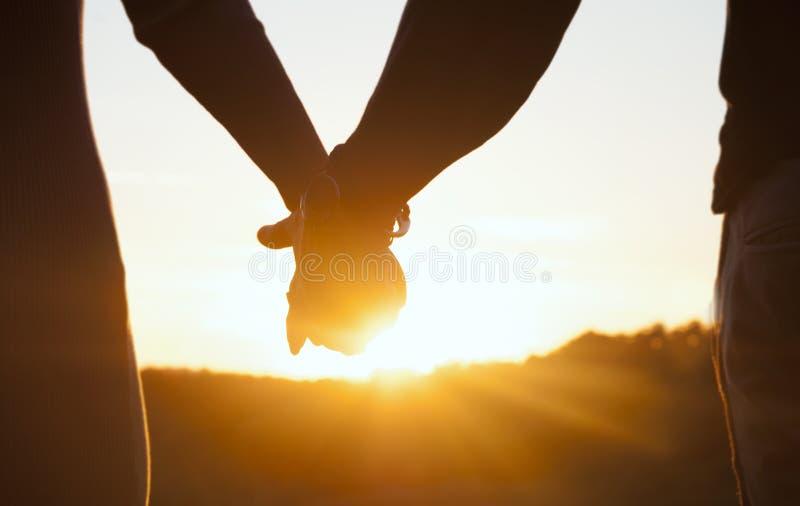 握手和观看美好的日落的浪漫夫妇 图库摄影