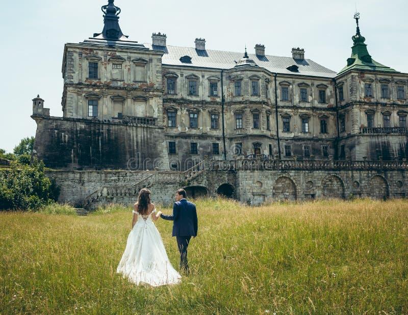 握手和走到老城堡的时髦的新婚佳偶夫妇的全长后面看法在晴朗期间 免版税库存照片