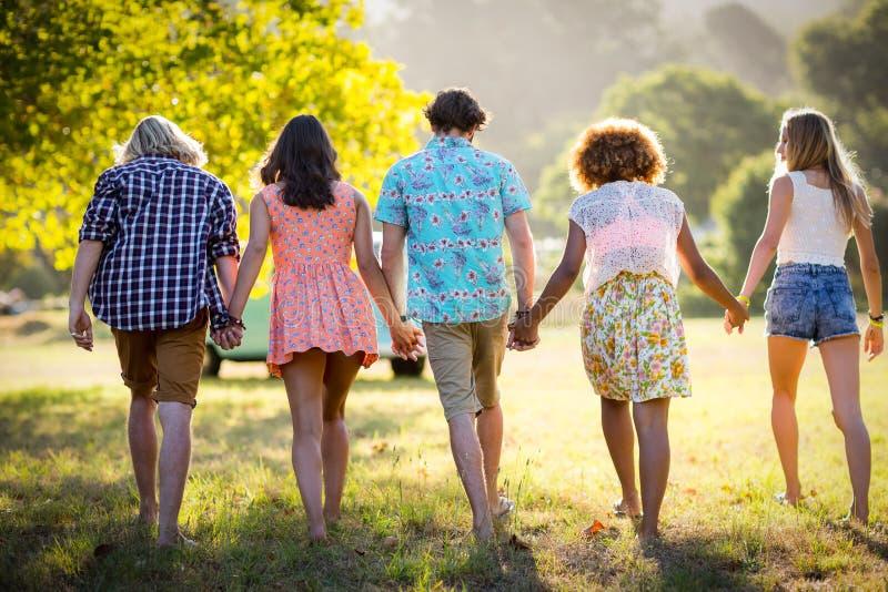 握手和走在公园的朋友 免版税库存图片