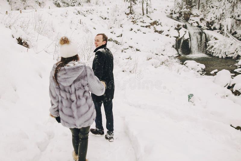 握手和走在冬天多雪的mountai的时髦的夫妇 库存照片