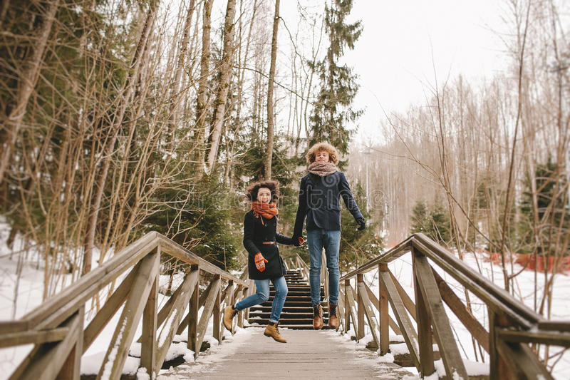 握手和跳跃在冬天公园的年轻愉快的夫妇 库存图片