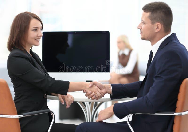 握手商务伙伴在谈判桌上 库存照片