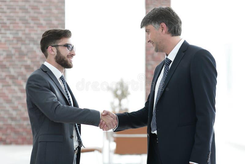 握手在业务会议的商人在办公室 库存照片