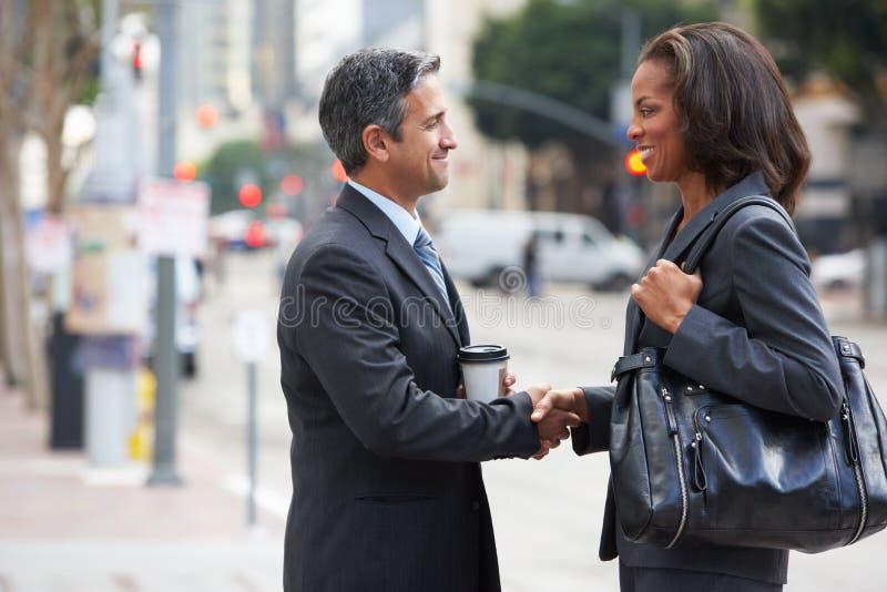 握手在街道的商人和女实业家 库存照片