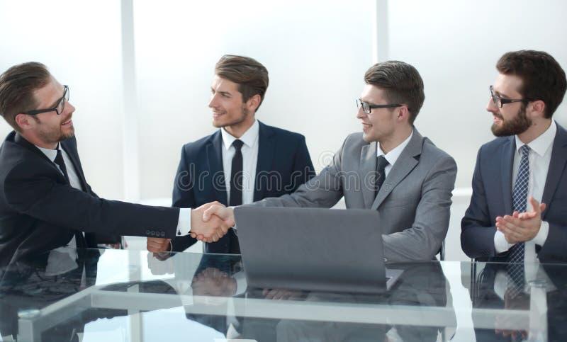 握手坐在谈判桌上的商务伙伴 免版税库存图片