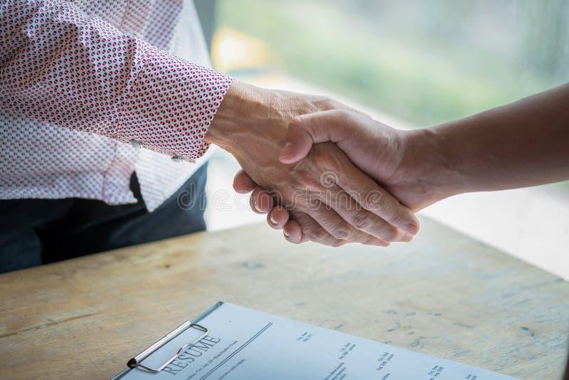 握手成功工作采访 有的求职者采访 握有简历的手在书桌上 给握手的雇主 免版税库存图片