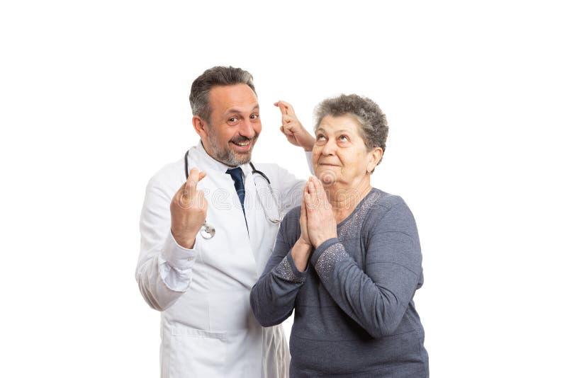握手指的军医横渡了和祈祷为爆发的患者 图库摄影