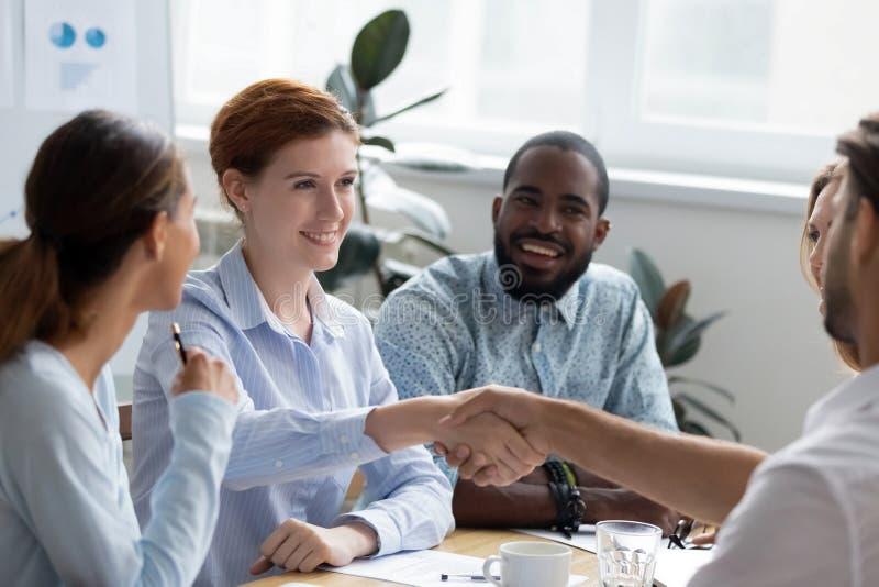 握手的不同种族的女实业家招呼公司客户 库存照片