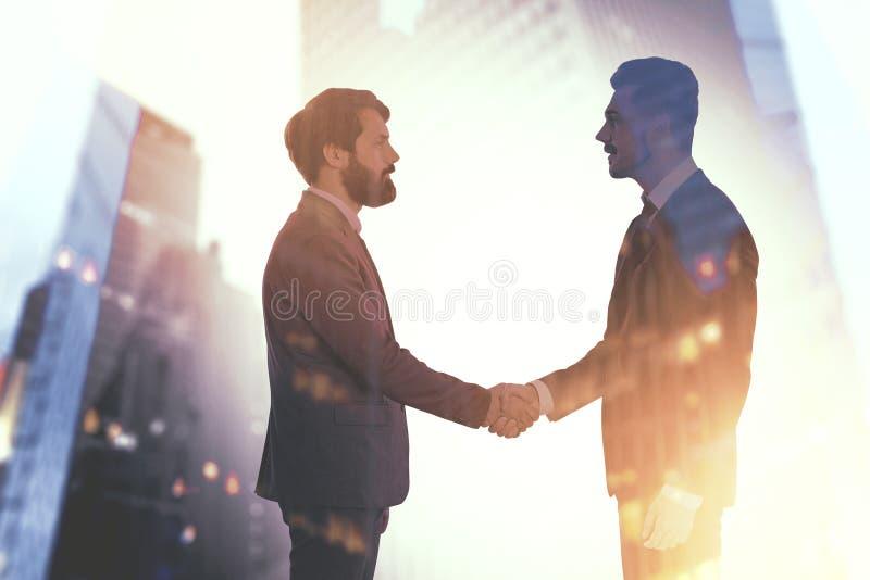 握手的两个商人在城市 库存图片