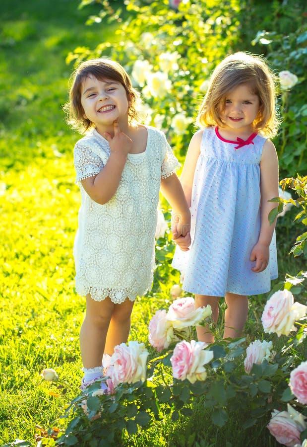握手的两个女孩在夏天庭院里在好日子 库存照片