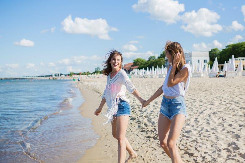 握手的两个女性朋友走在海滩笑 库存照片