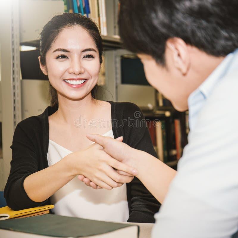 握手的两位亚裔大学生在图书馆里 免版税库存照片