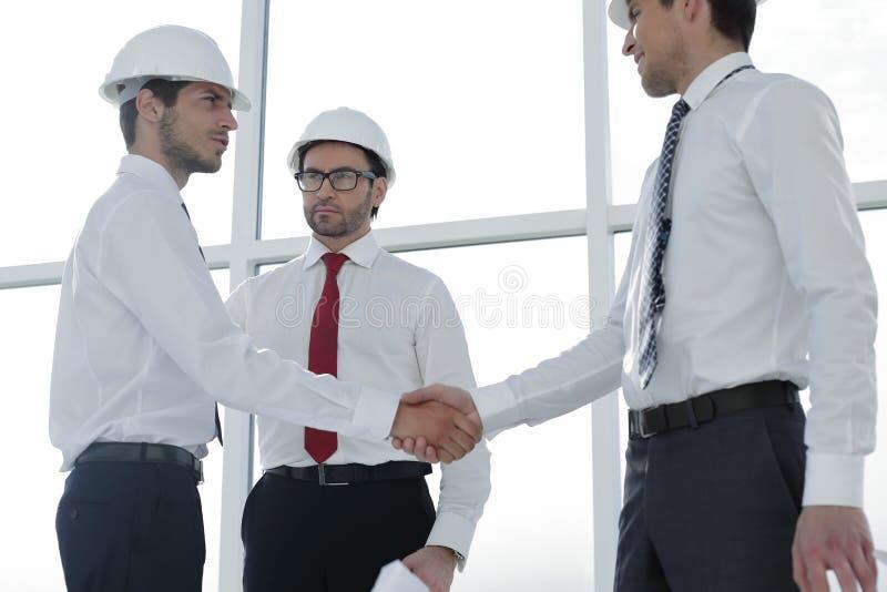 握手的两位建筑师在一次会议以后在办公室 库存照片