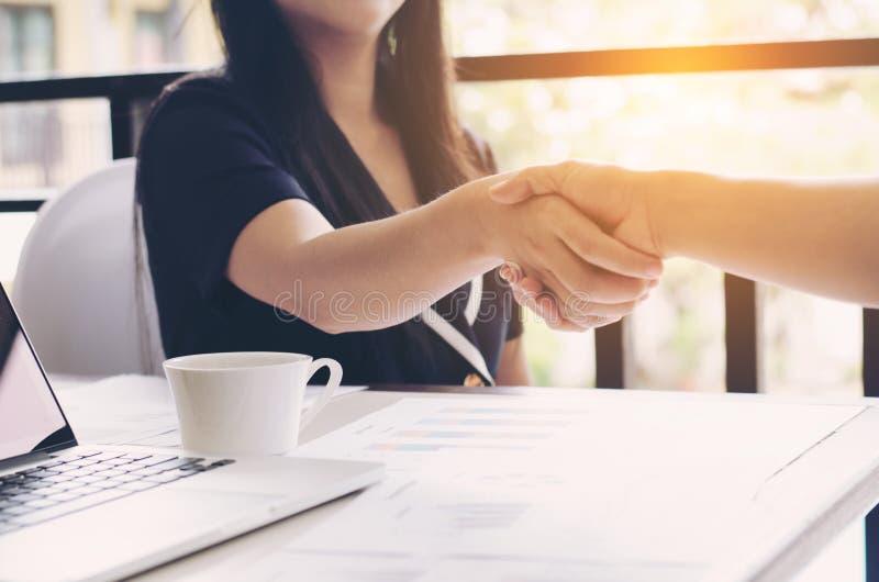 握手的两名商人妇女特写镜头在工作地点 免版税库存图片