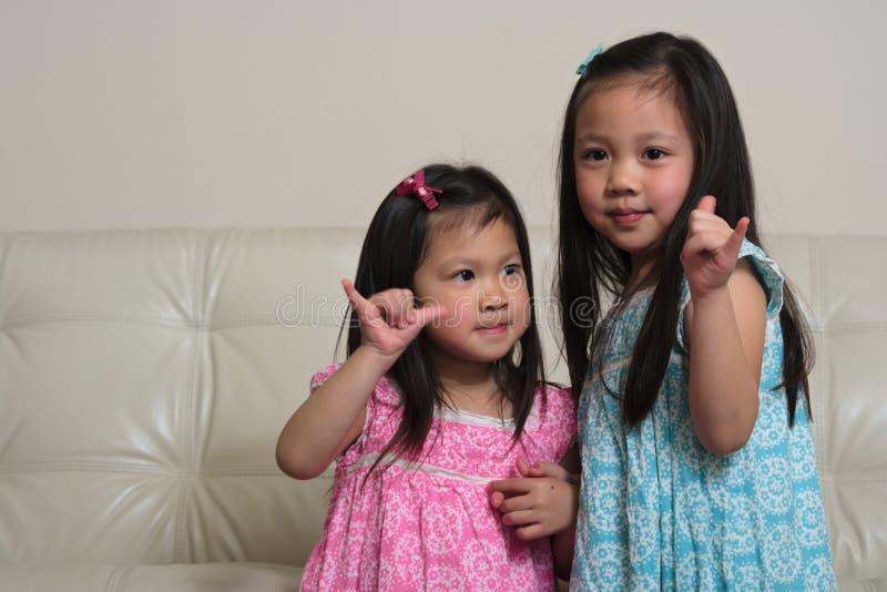 握手的亚裔姐妹喜欢冲浪者 库存照片