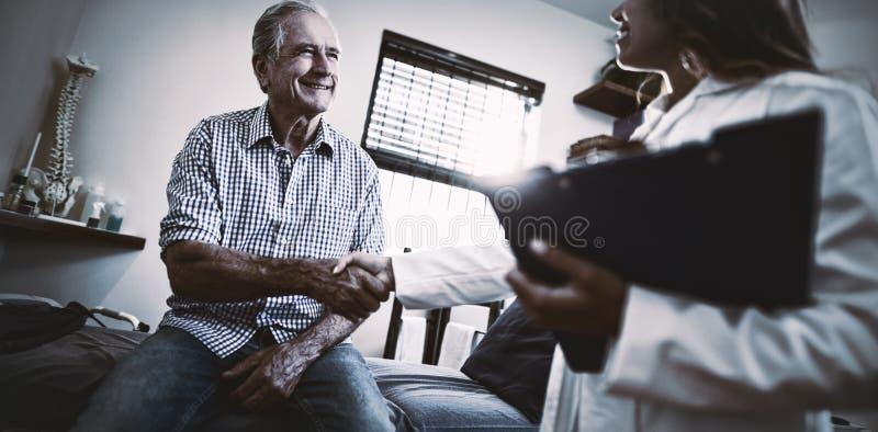 握手的低角度观点的女性治疗师和资深男性患者 免版税库存照片