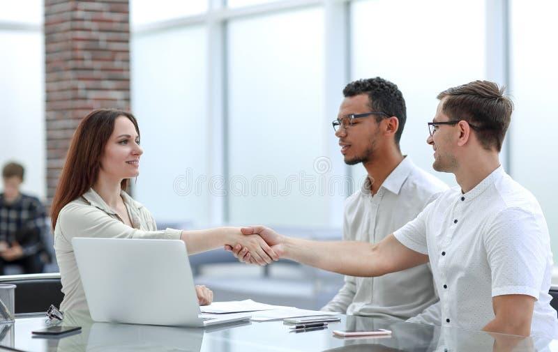 握手的商人和女实业家证实他们的成交 免版税库存照片