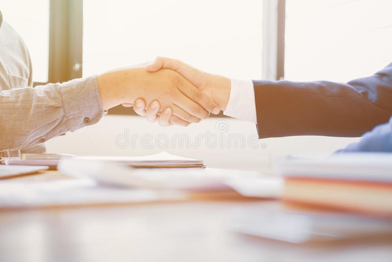 握手的商人在候选会议地点,成功的成交在见面以后 橙色光口气 免版税库存图片