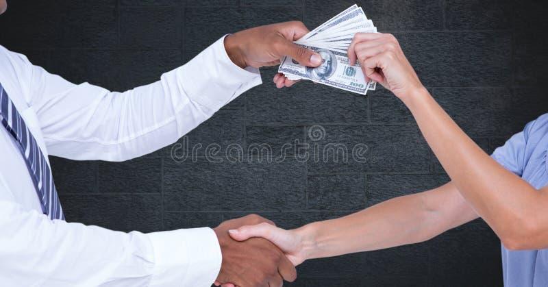 握手的商人,当拿着代表腐败概念时的金钱 图库摄影