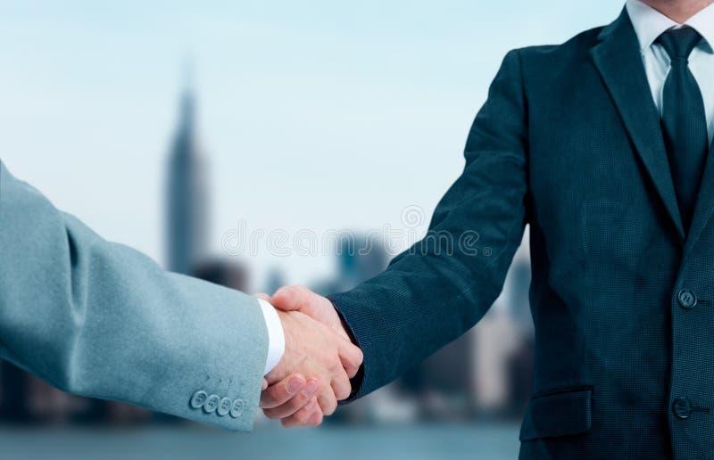 握手的商人,结束会议 商务伙伴在城市的背景中 免版税库存图片