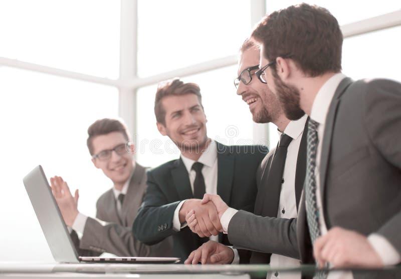 握手的商务伙伴坐在办公室桌上 图库摄影