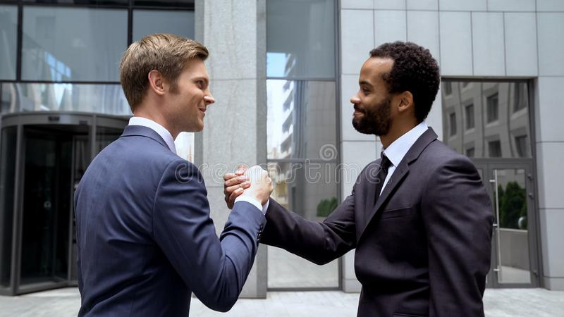 握手的多种族伙伴在成功的成交,在起动的配合以后 图库摄影