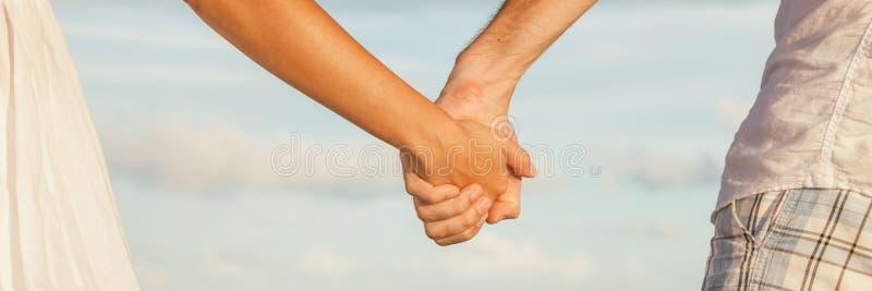 握手的夫妇横幅背景约会浪漫日落海滩步行 免版税图库摄影