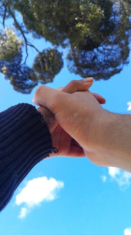 握手的夫妇看天空 免版税库存图片
