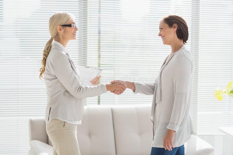 握手的妇女和治疗师 免版税库存照片
