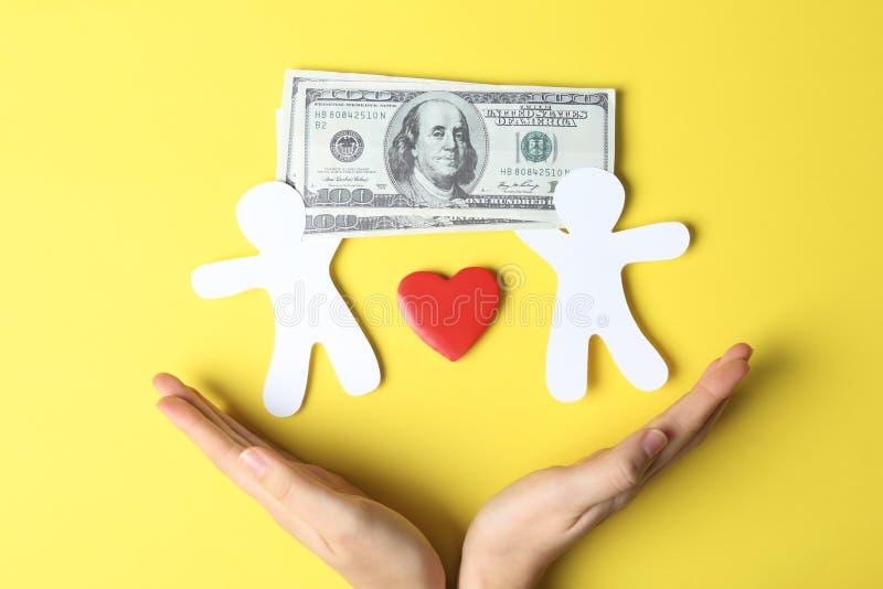 握手的妇女在人、心脏和金融法案附近纸剪影在颜色背景,顶视图 库存图片
