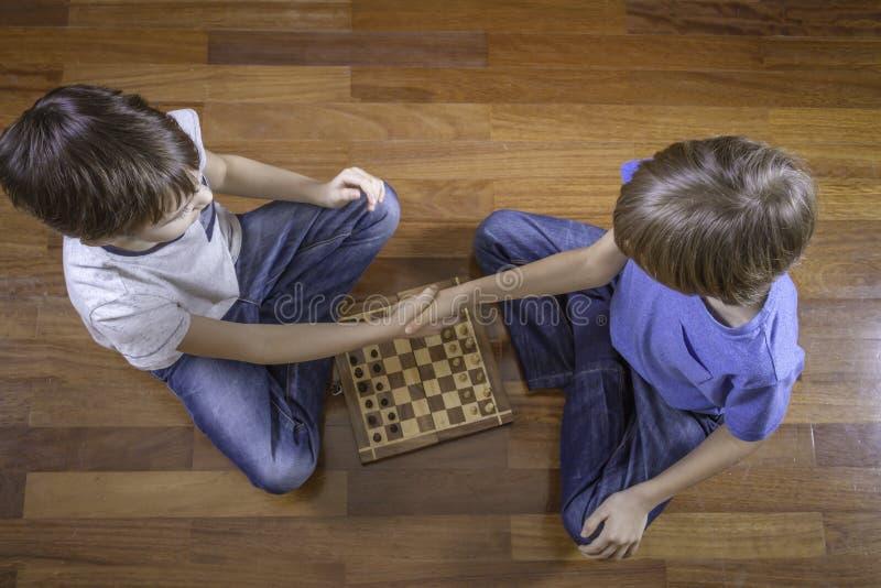 握手的孩子在棋前坐木地板 顶视图 库存照片