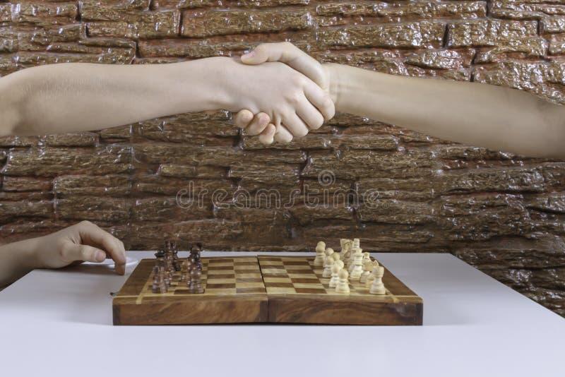 握手的孩子的手在棋前 免版税库存照片
