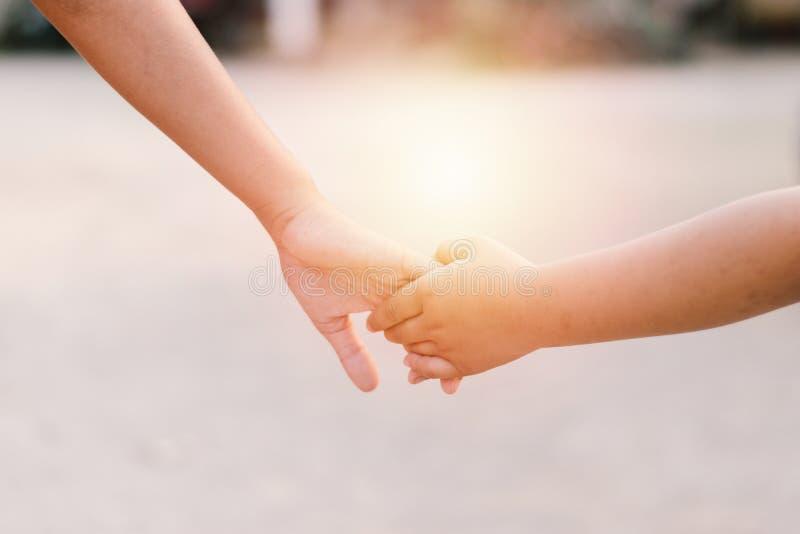 握手的孩子,当走在日落时 库存照片