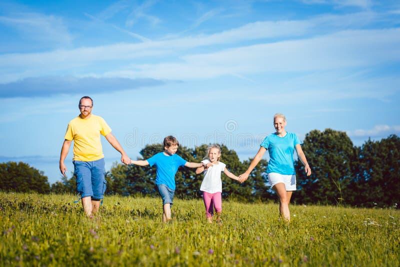 握手的家庭运行在草甸 免版税库存图片