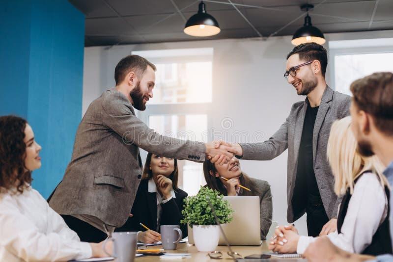 握手的年轻商人在办公室 完成的成功的会议 图库摄影