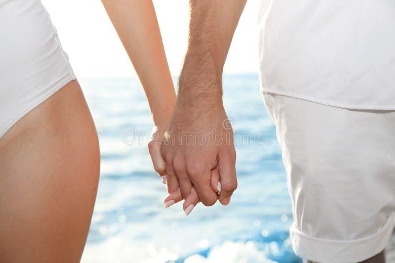 握手的年轻夫妇在晴天临近海 图库摄影