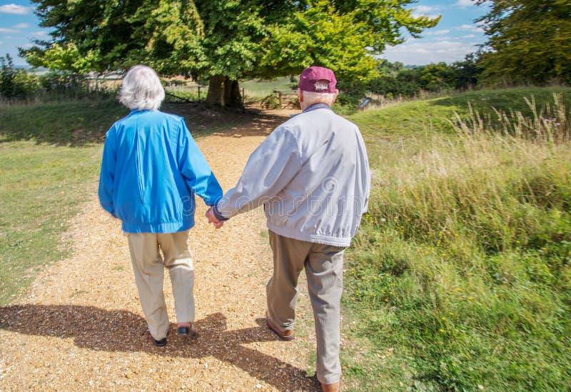握手的年长夫妇,当参观英国乡下时 库存照片