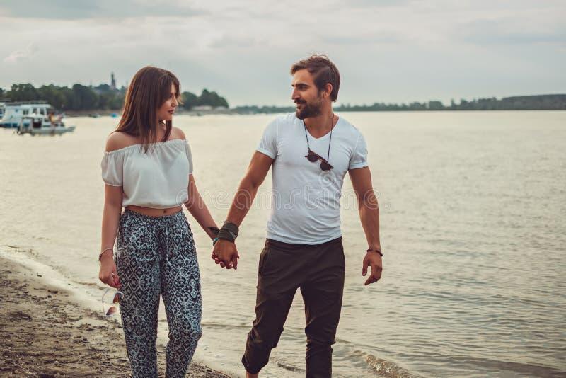 握手的微笑的夫妇,当走在海滩时 免版税库存图片