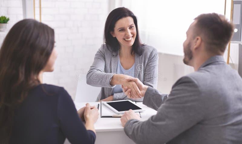 握手的微笑的女性保险经纪人和年轻家庭 免版税库存图片