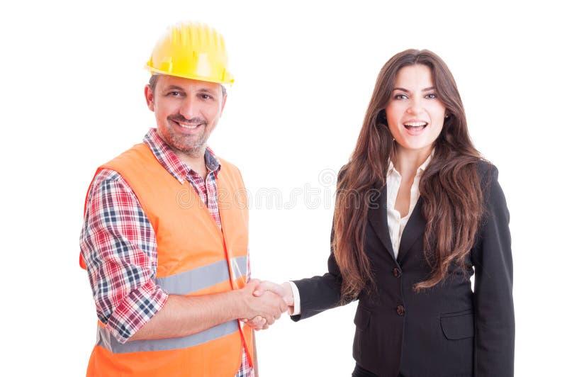 握手的微笑的承包商和女商人 免版税图库摄影
