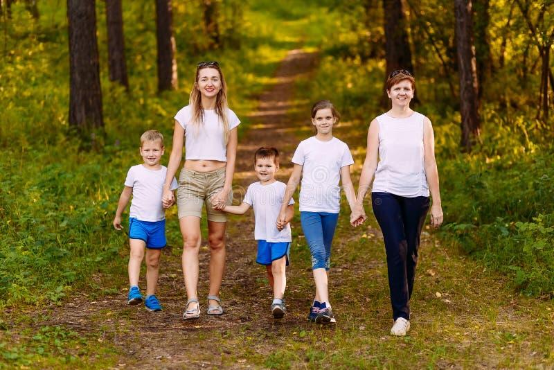 握手的微笑的母亲和孩子 大幸福家庭、两名妇女和三个孩子白色T恤的 免版税库存照片